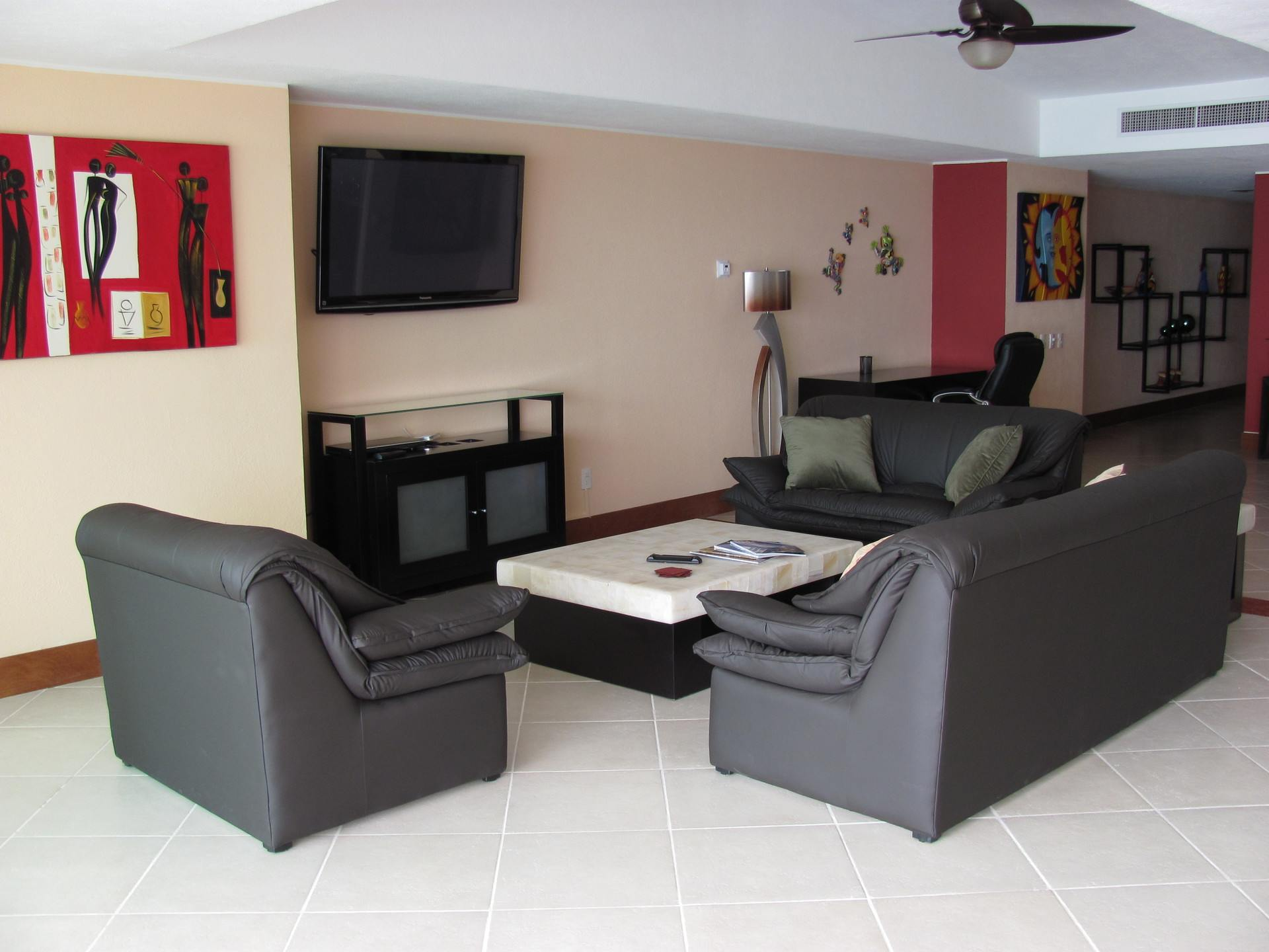 Artwotrk on the walls of the living room with TV in this 2 bedroom vacation condo for rent in Grand Venetian Puerto Vallarta