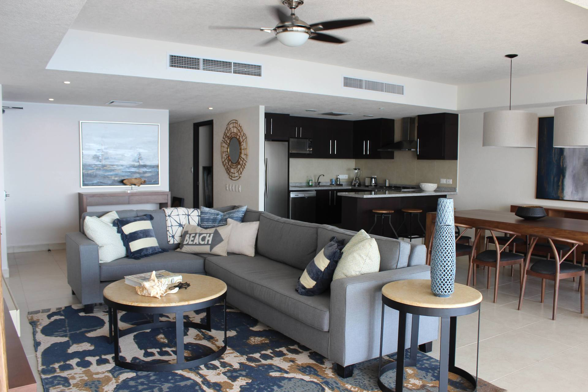 Modern and contemporary living room, couch, kitchen, and dining table of this 2 bedroom vacation rental condo of Grand Venetian Puerto Vallarta