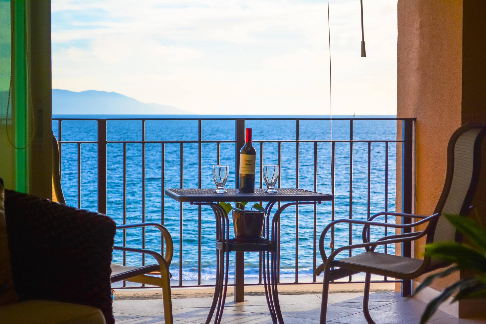 Terrace table and chairs with a bottle of wine overlooking the oceanfront view of this 1 bedroom vacation rental condo in Grand Venetian Puerto Vallarta